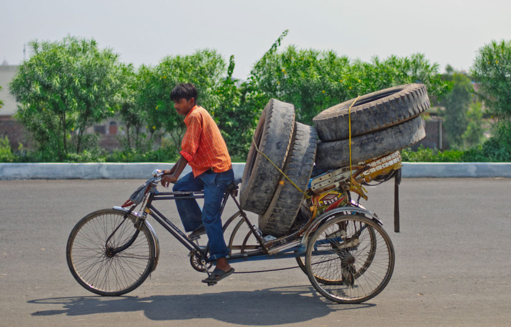 A rickshaw loaded with truck tires.