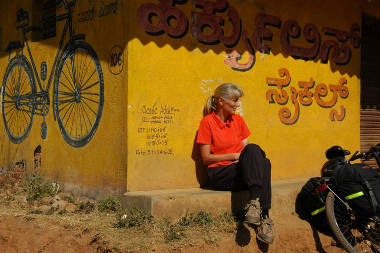 A western cyclist leans against a building with an Indian bicycle painted on it during a bicycle tour of South India.