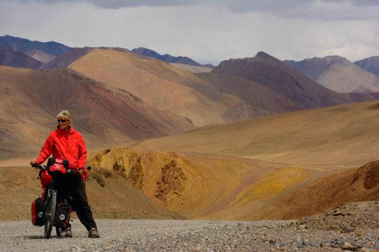 touring cyclist stands on top of ak baital pass
