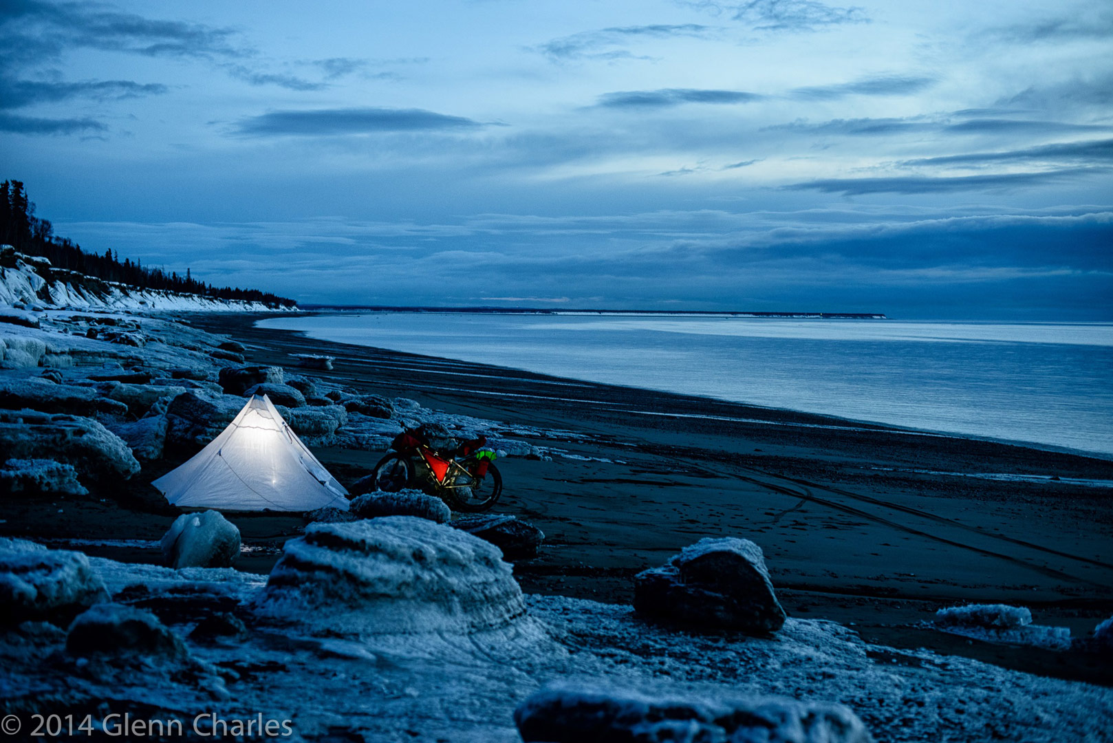 Glen Charles bike camping on a beach in Alaska.