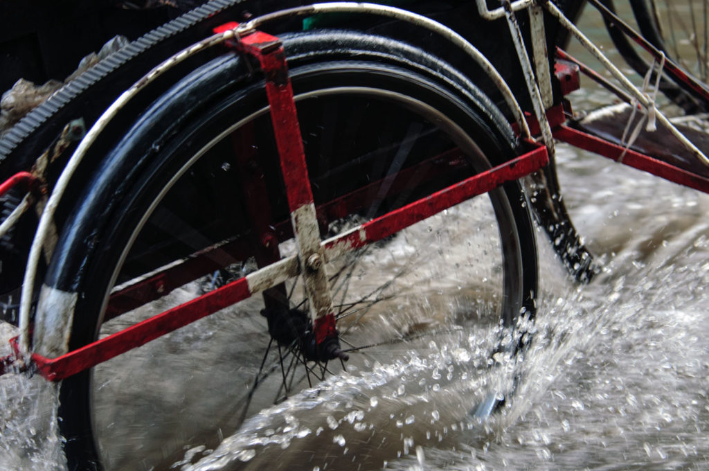 A rickshaw wheel churns up the water on a Myanmar street.