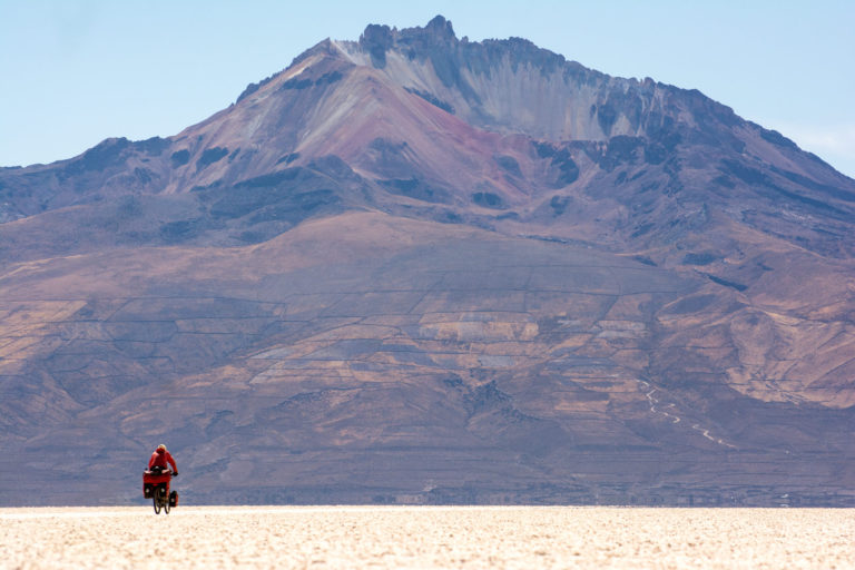 Cycling towards a volcanoe on the Salar de Uyuni in Bolivia.