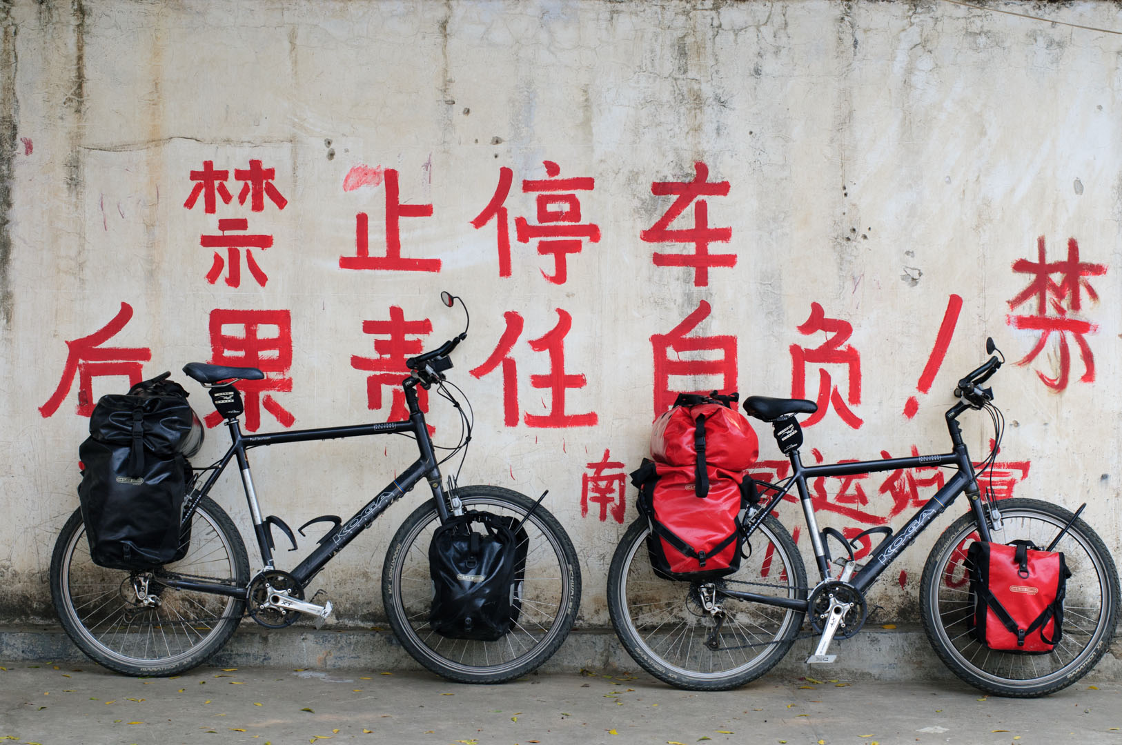 Touring bicycles are leaned against a wall with Chinese writing on it.