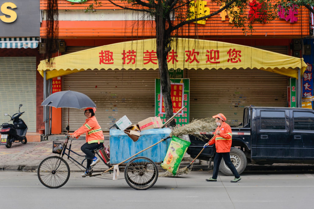 Two cycling Chinese street cleaners.