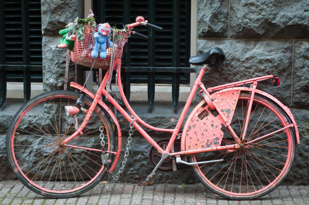 A pink bicycle leans against a wall in Amsterdam, the Netherlands.