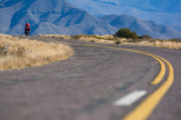 A small red cyclist heads towards the mountains in Northern Argentina.