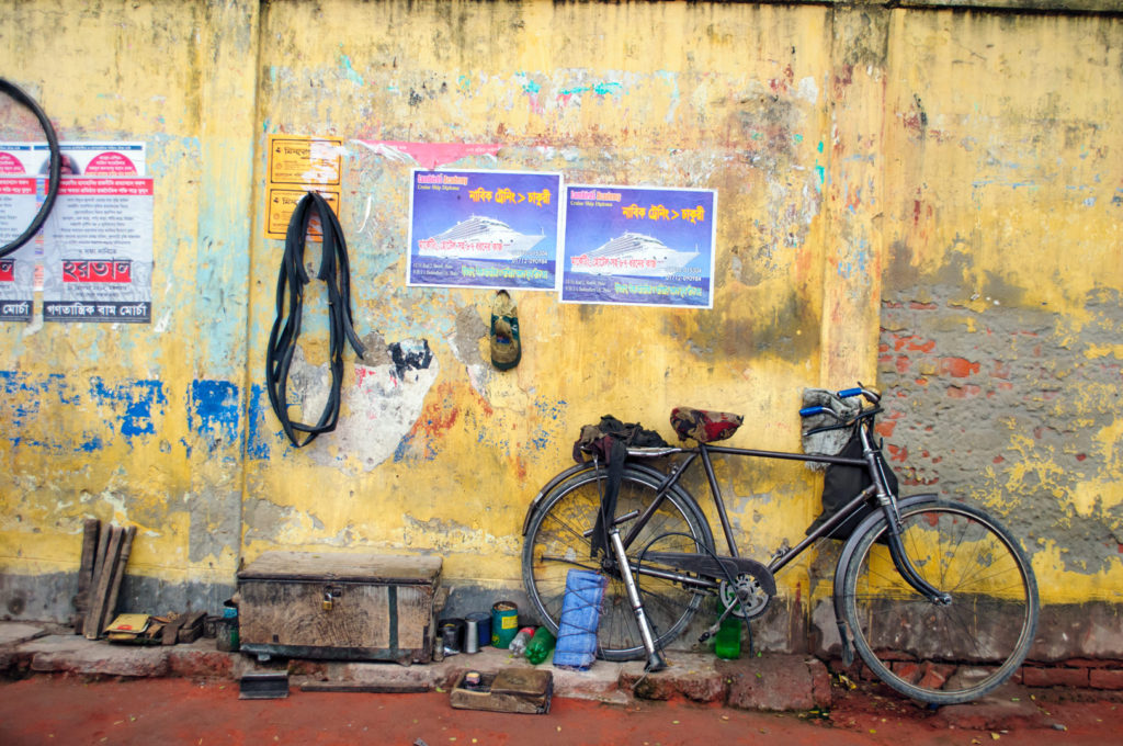 A bicycle is parked against a yellow wall in Bangladesh.