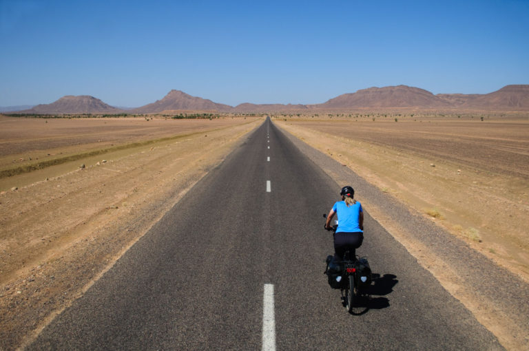 A blue touring cyclist pedals towards brown hills in the Morroccan desert.