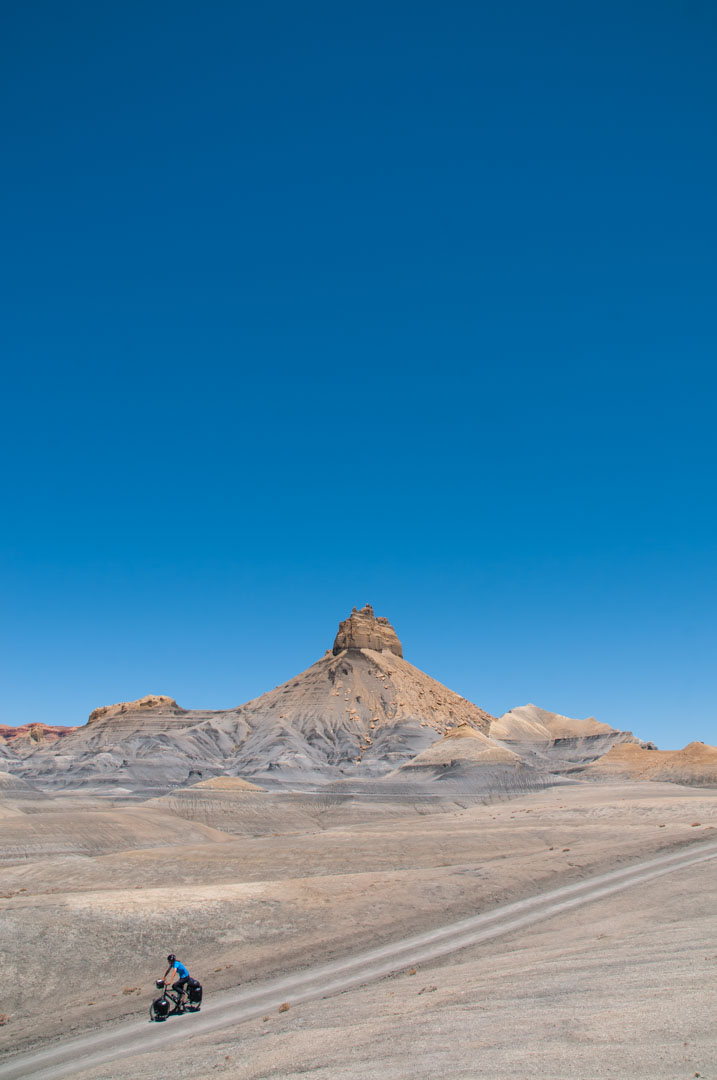 a blue cyclist pedals through the grey desert in Utah.