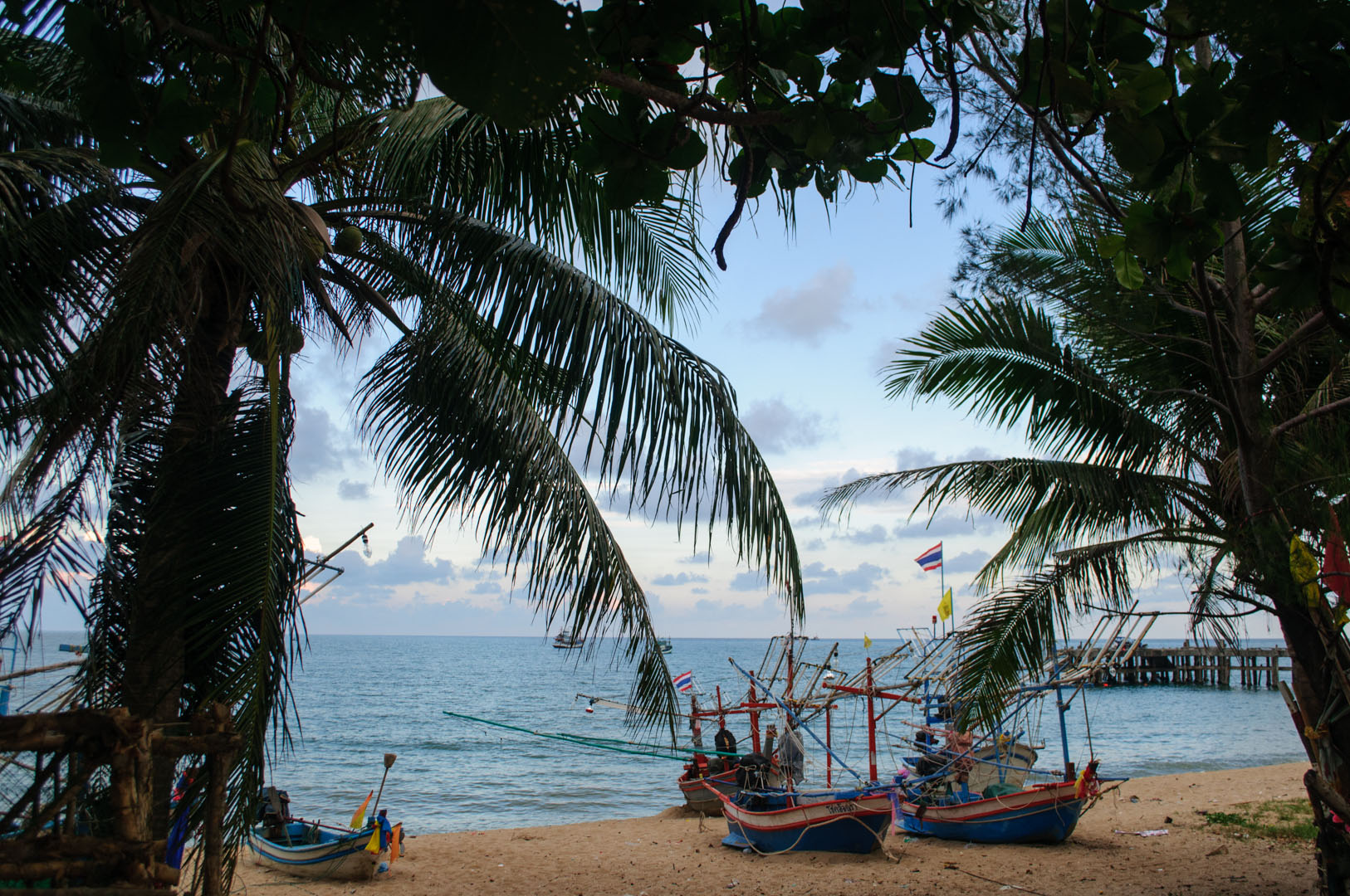 Thailand beach with palm trees and fishing boats.